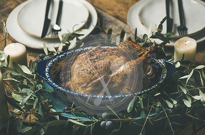 Whole roasted chicken in tray for Christmas eve celebration decorated with olive tree branch