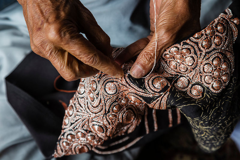Man Sewing Copper Ornamentation on to Outfit