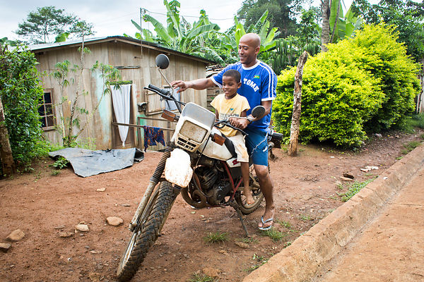 Joel, 7 ans, et son père José sur sa moto devant leur maison à Santana, Sao Tomé / Joel, 7 years old, and his father José on ...
