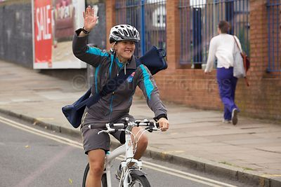 Police Officer Cycling with Paralympic Torch on her Back