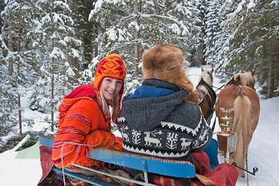 Austria, Salzburger Land, Couple riding in sleigh, smiling, portrait