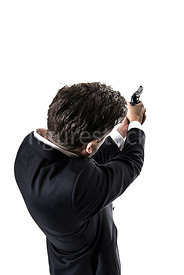 A mystery man in a suit, aiming a gun – shot from above.