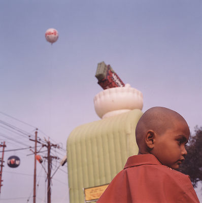 A child whose head has been shaved and a balloon at the Kumbh Mela