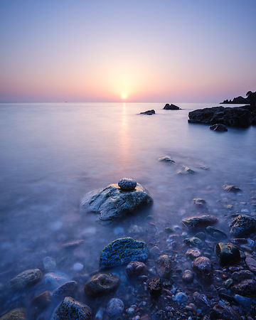A colourful spring sunrise over Torbay with warm light glinting off the wet rocks, Anstey's Cove, Torquay, Devon, UK