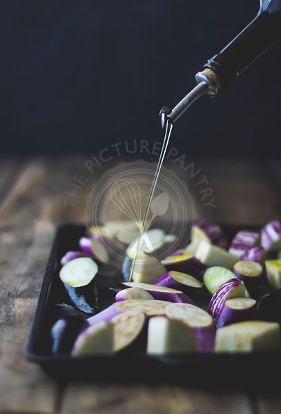 Eggplant. Oil being drixxled over sliced eggplant.