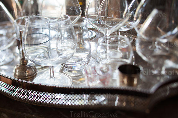 Empty snifter liquor glasses on a reflective silver tray