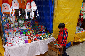 Boy playing next to stall selling games and decorations in street market, La Paz, Bolivia