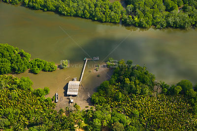 Aerial view of river, mangroves and fishing building in lowland rainforest, Rio Sungai Kinabatangan, Sabah, Borneo, Malaysia....