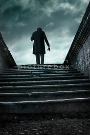 An atmospheric image of a mystery man in a hat, standing at the top of some steps to a old graveyard.