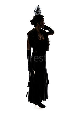 A silhouette of a vintage 1920s - 1930s woman in a long black dress with a fur, headband and feather – shot from eye level.