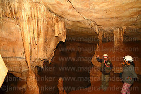 Guide and tourist looking at chandelier stalactite formations in Umajalanta caves, Torotoro National Park, Bolivia