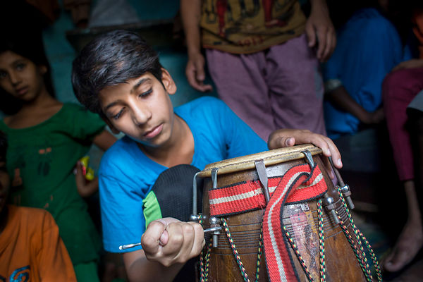 Kishan, 12 ans accorde son dholak, Kathputli Colony, Delhi, Inde / Kishan, 12 years old tuned his dholak, Kathputli Colony, D...