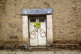 Adobe wall and old wooden door with guitar stencils and for sale sign, Tarija, Bolivia