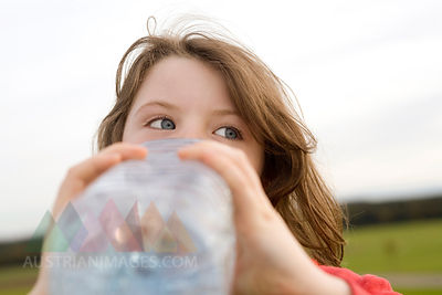 Girl (7-9) drinking from water bottle, close-up