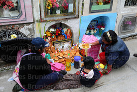 Family sitting next to tomb of deceased relative in cemetery during Todos Santos festival, La Paz, Bolivia