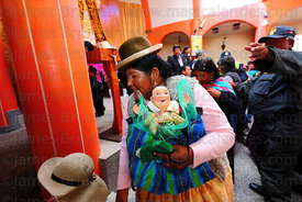Aymara lady with ekeko inside church, Alasitas festival, Puno, Peru
