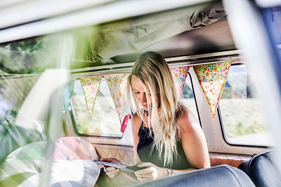 Woman using tablet inside a van