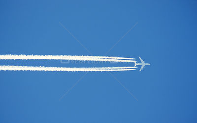 Vapour trails left in blue sky by jet aircraft. Scotland, UK