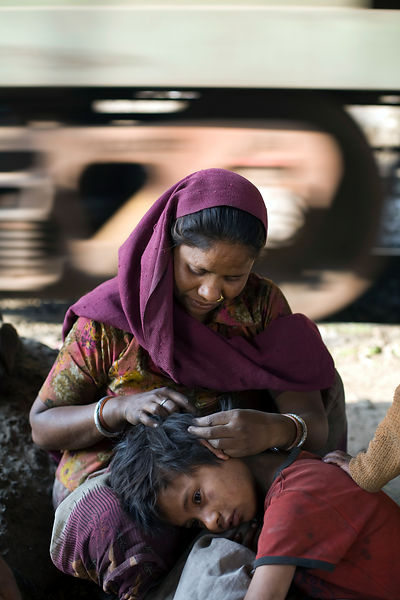 India - New Delhi - A mother picks at her child's hair for fleas