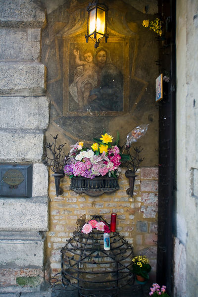 Italy - Verona - A Christian shrine on the street with candles and fresh flowers showing Christ and the Virgin