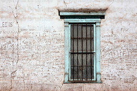 Window and graffiti carved into adobe wall of house, Matilla, Region I, Chile