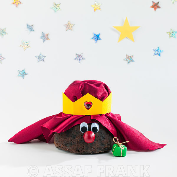 Christmas pudding king with gifts on whtie background