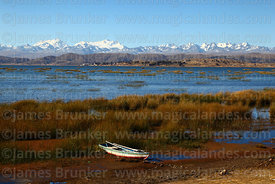 Rowing boat and totora reeds (Schoenoplectus californicus ssp. tatora) on shore of Inner Lake, peaks of Cordillera Real in background, Lake Titicaca, Bolivia