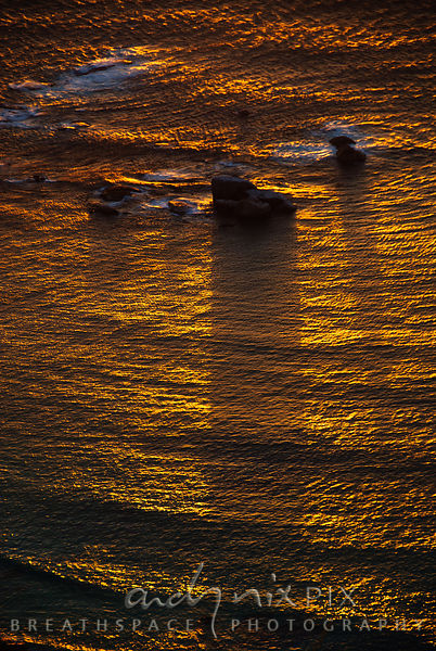 Golden sunlight on the sea with rocks at sunset
