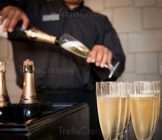 A male server pours glasses of white sparkling wine for guests at a party