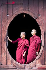 Two monks standing in a oval window of a monastery, Myanmar