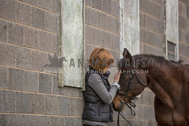 woman petting horses head standing next to barn