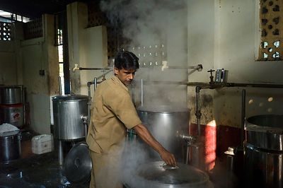 India - Kozhikode - A kitchen hand works through the steam in the kitchens of the Medical College brach of the Indian Coffee ...