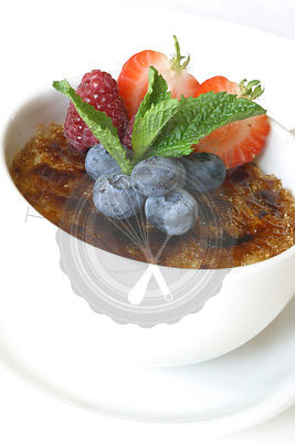 Creme brulee decorated with various fruit.  Served in a white dish.