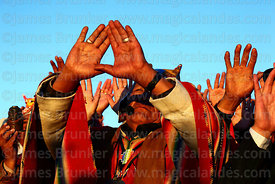 An Aymara shaman or amauta holds up his hands to receive the sun's energy at sunrise during Aymara New Year celebrations, Tiw...