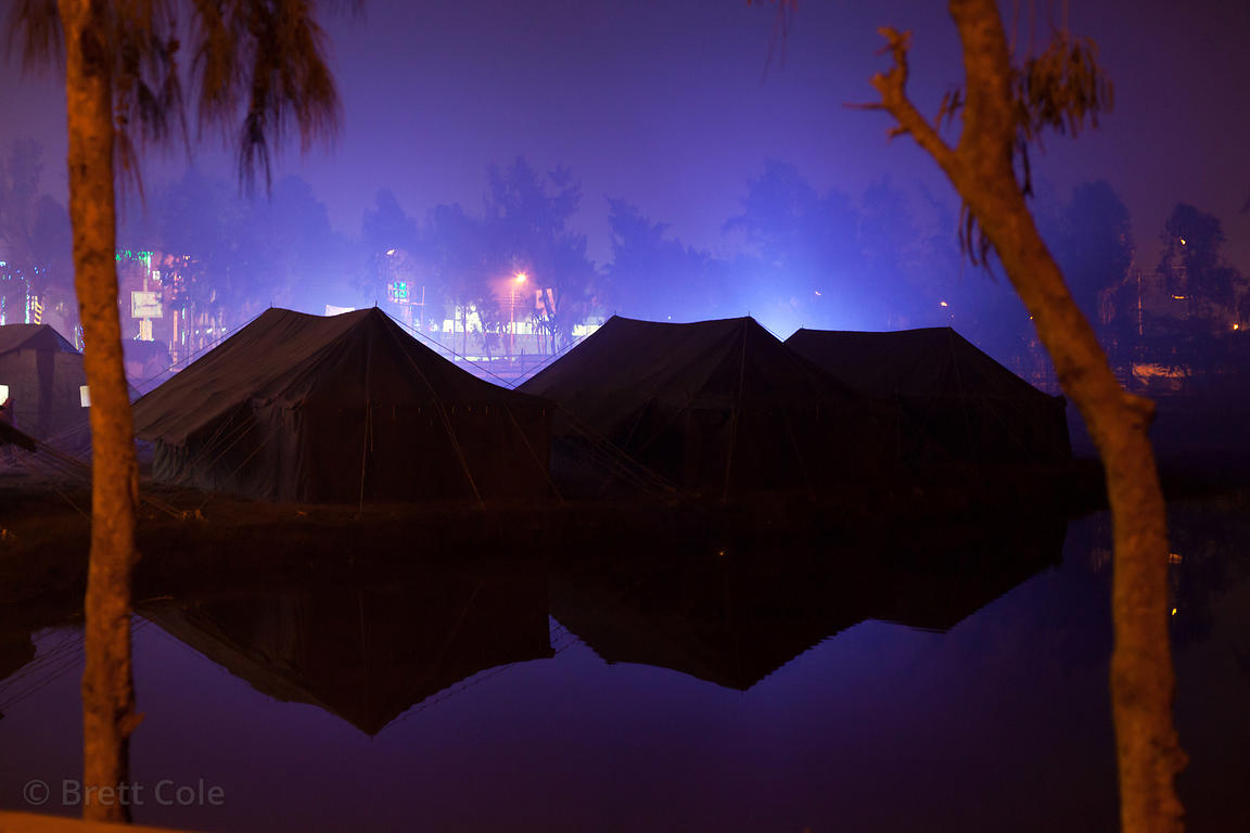 Tents are reflected into a pond at night at the Gangsagar Mela, Sagar Island, India.