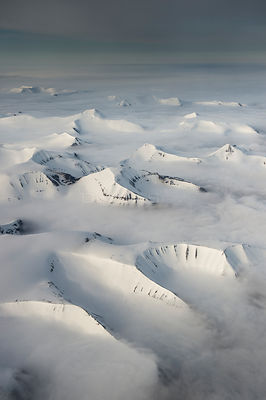 Aerial view of the mountains of southern Spitsbergen covered in snow with low clouds, Svalbard, Norway, June 2013.