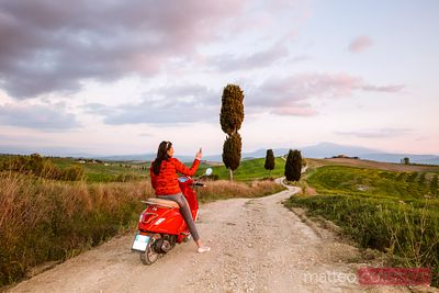Tourist riding a motorcycle in Tuscany at sunset