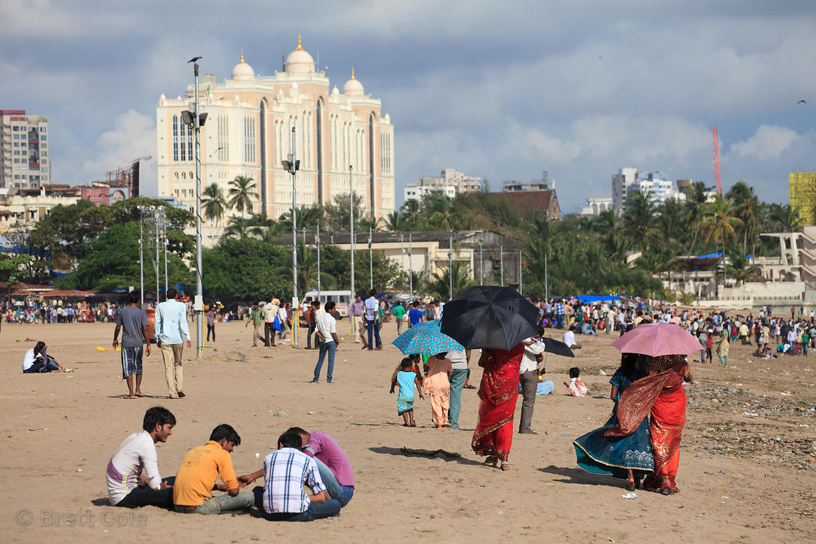 People stroll in Chowpatty Beach, Mumbai, India. In the background in Saifee Hospital.