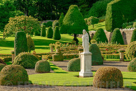 A stature in a beautiful formal garden settinh in autumn.