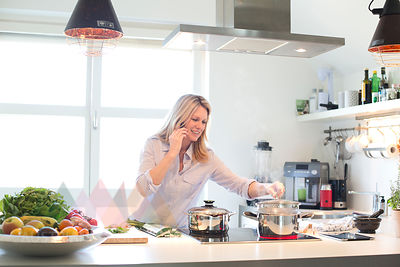 Smiling woman on cell phone cooking in kitchen