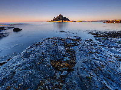 Sunrise with warm light making the granite walls golden at St Michael's Mount in Marazion, Cornwall, UK