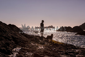 silhouette of a man standing with his dog at the edge of the water during sunset
