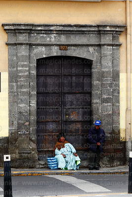 Aymara couple resting in colonial doorway, La Paz, Bolivia
