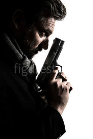 A semi-silhouette of a mystery man in a big coat, holding a gun – shot from eye level.