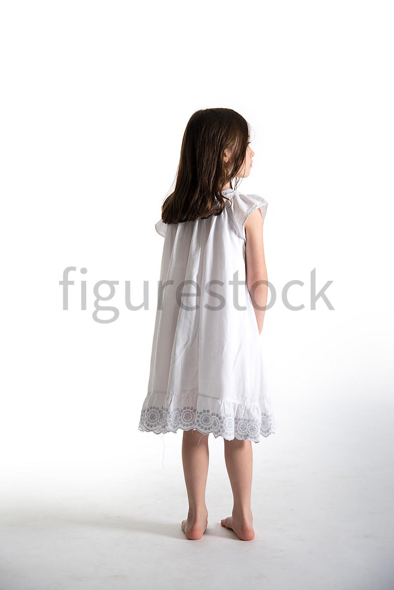 A Figurestock image of a little girl, standing in a night dress, looking away – shot from eye level.