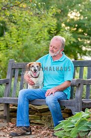 older man sitting on bench looking affectionately at small dog