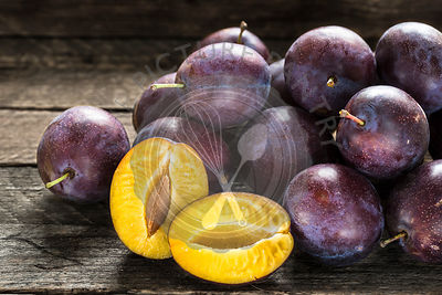 Fresh blue plums on wooden table
