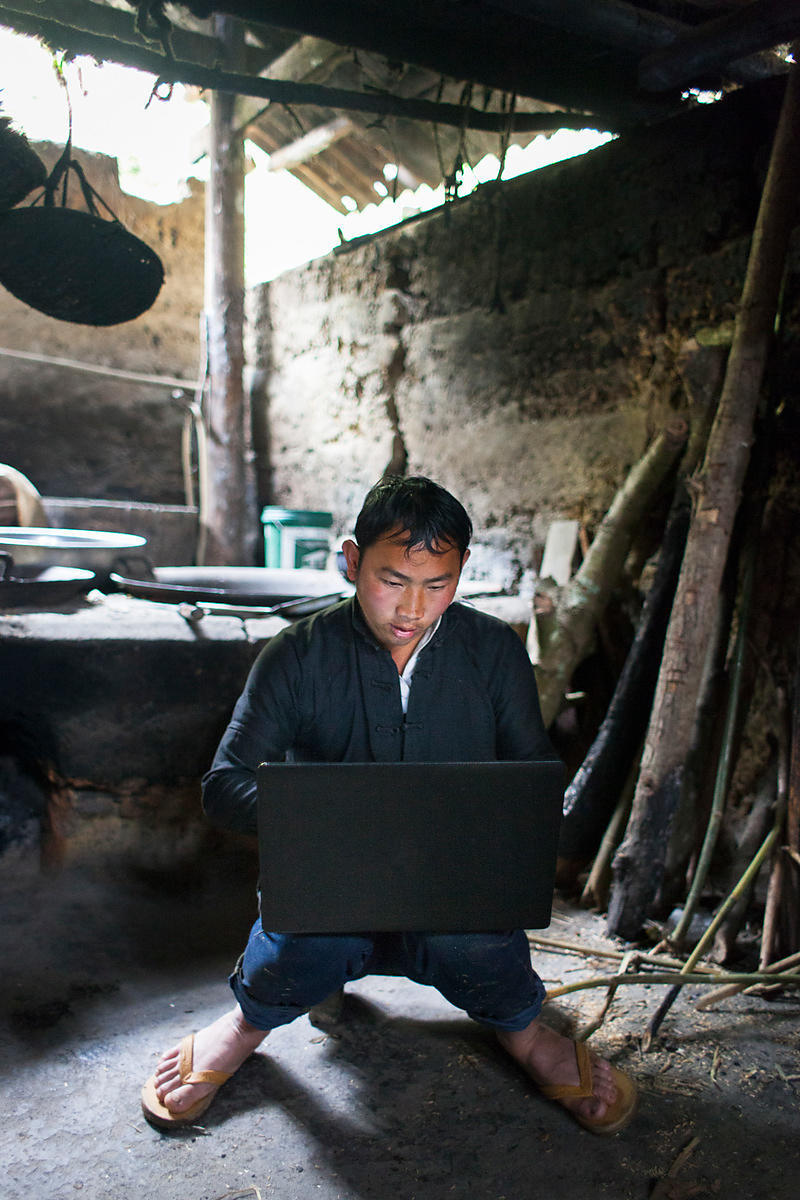 Homme dans sa cuisine traditionelle avec son ordinateur, Bac Ha, Vietnam / Man in traditional cuisine with his computer, Bac ...