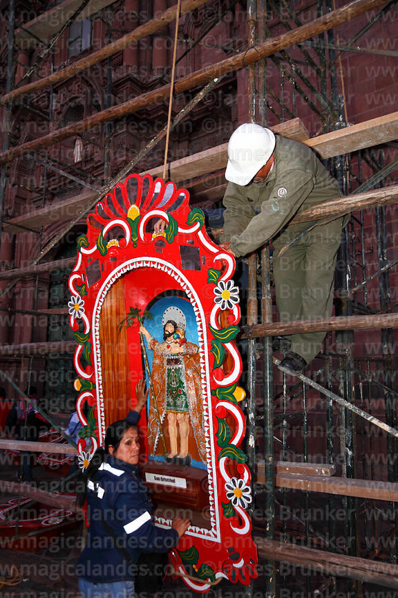 Workers putting up decorations for Corpus Christi festival in front of Compañia de Jesus church , Cusco , Peru