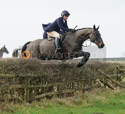 Phoebe Buckley jumping a hedge above Wilson's Covert